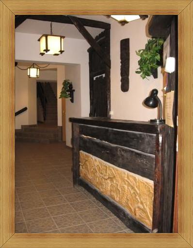 Recepcja Noclegi Restauracja SAK - wyposażona w stylowe rzeźbione meble z motywem kiści winogron zdobi hol recepcji